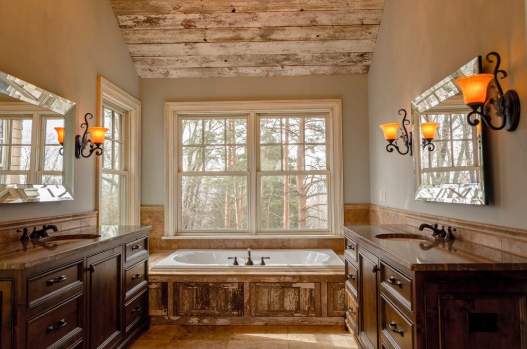 Very rustic bathroom with a bath in the center, set beneath a large window