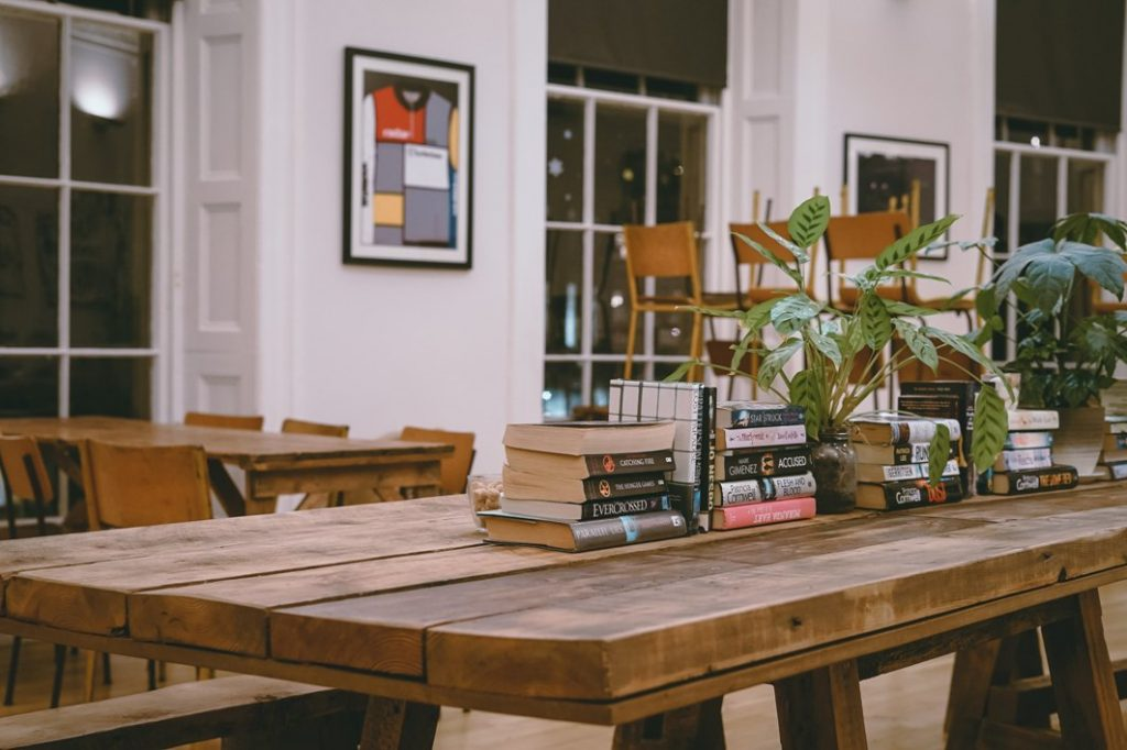 A wooden refectory style table with piles of books in the center and lots of pot plants