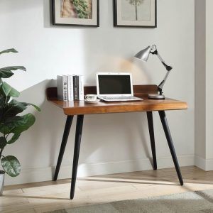 A retro walnut desk by Jual with a laptop on it and some books and an adjustable metal table lamp, set against a grey background