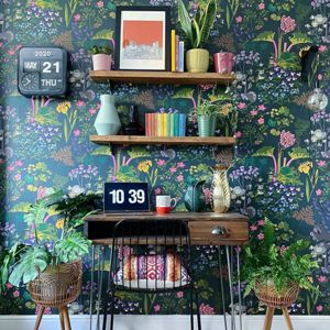 a home office location with desk and chair and shelves above and bright floral wallpaper in dark green blue