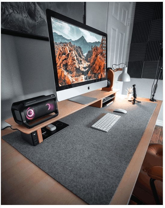 an image of a computer desk, large screen, keyboard and mouse, speaker setup and desk lamp