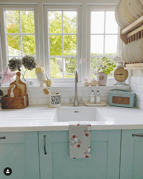 a country style kitchen in a soft green color