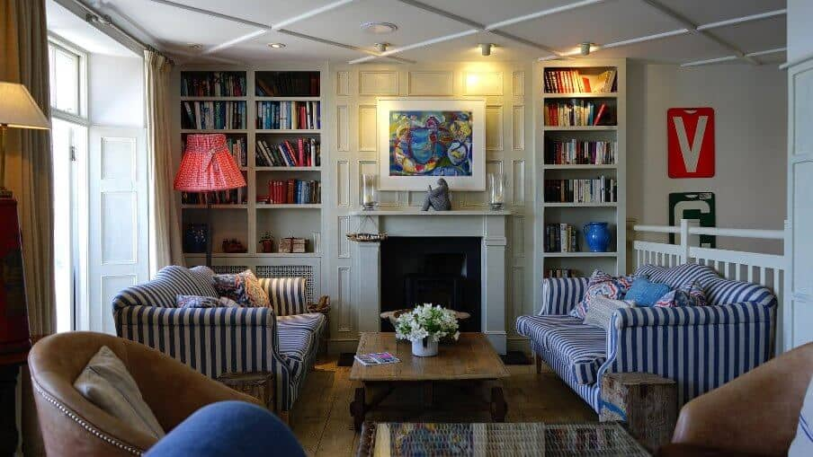 living room setting in front of a marble fire surround and book shelves either side