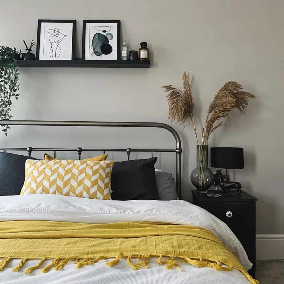 metal bed frame, white and yeloow bedding set against a grey wall