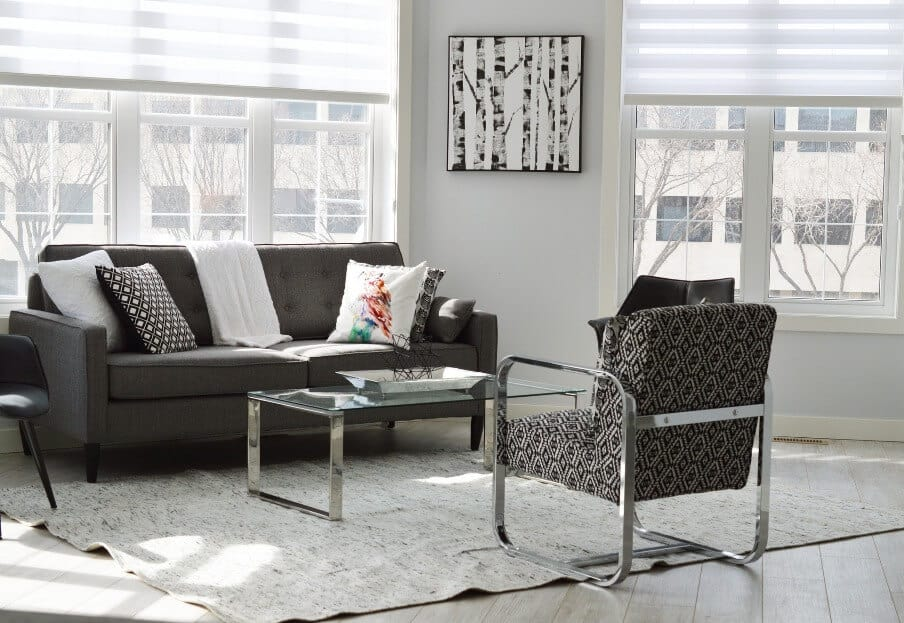 a living room setting with armchair and sofa with two areas of large windows behind