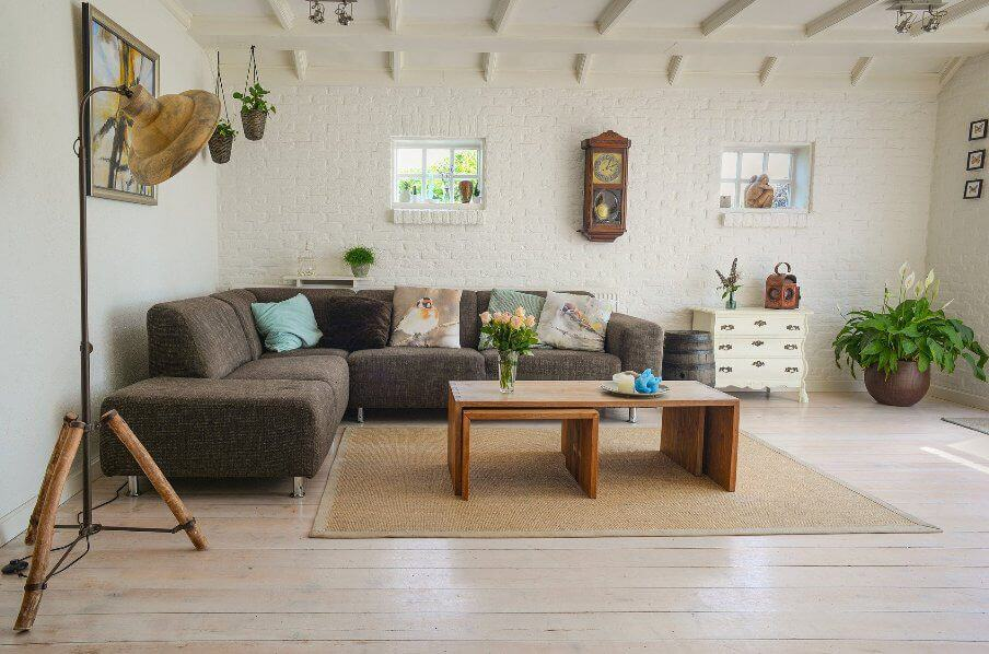 living room scetting with dark gray sectional sofa, large old brass spotlight for a floor mounted standard lamp.