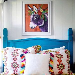 blue bedhead with cushions stacked against and picture of a donkey above
