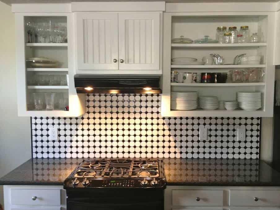 kitchen setting with wall cupboards and tiled splashback