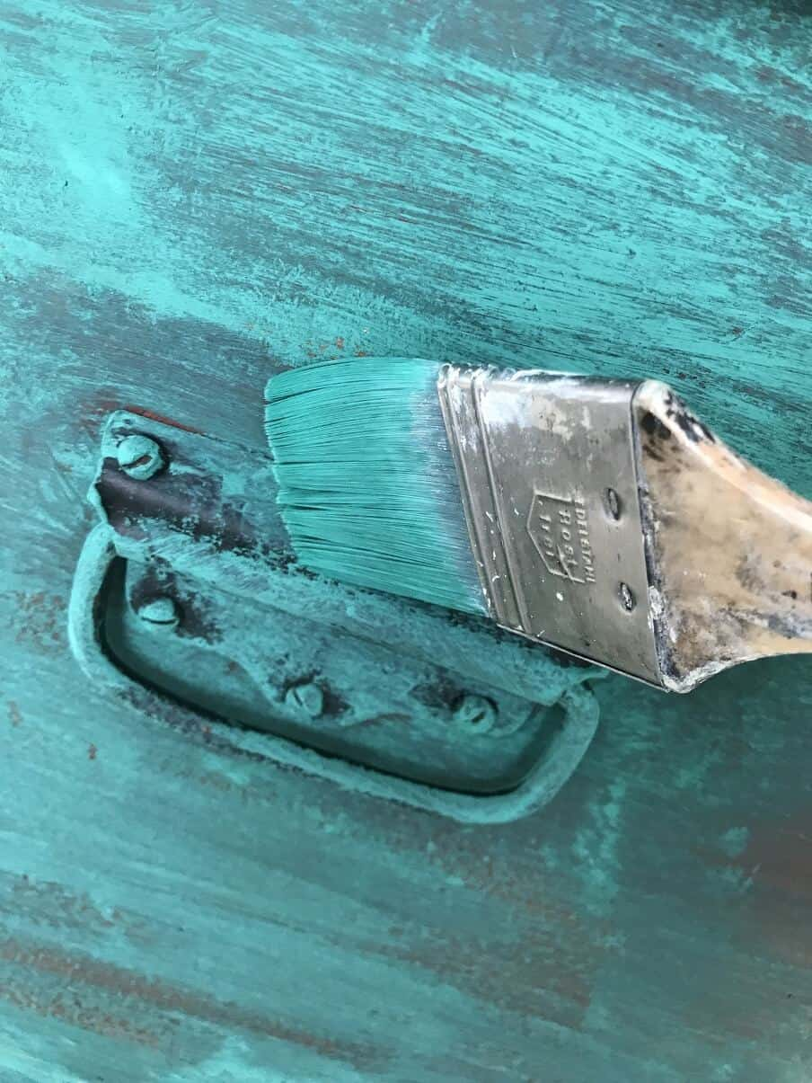 paint brush loaded with green blue paint repainting a trunk