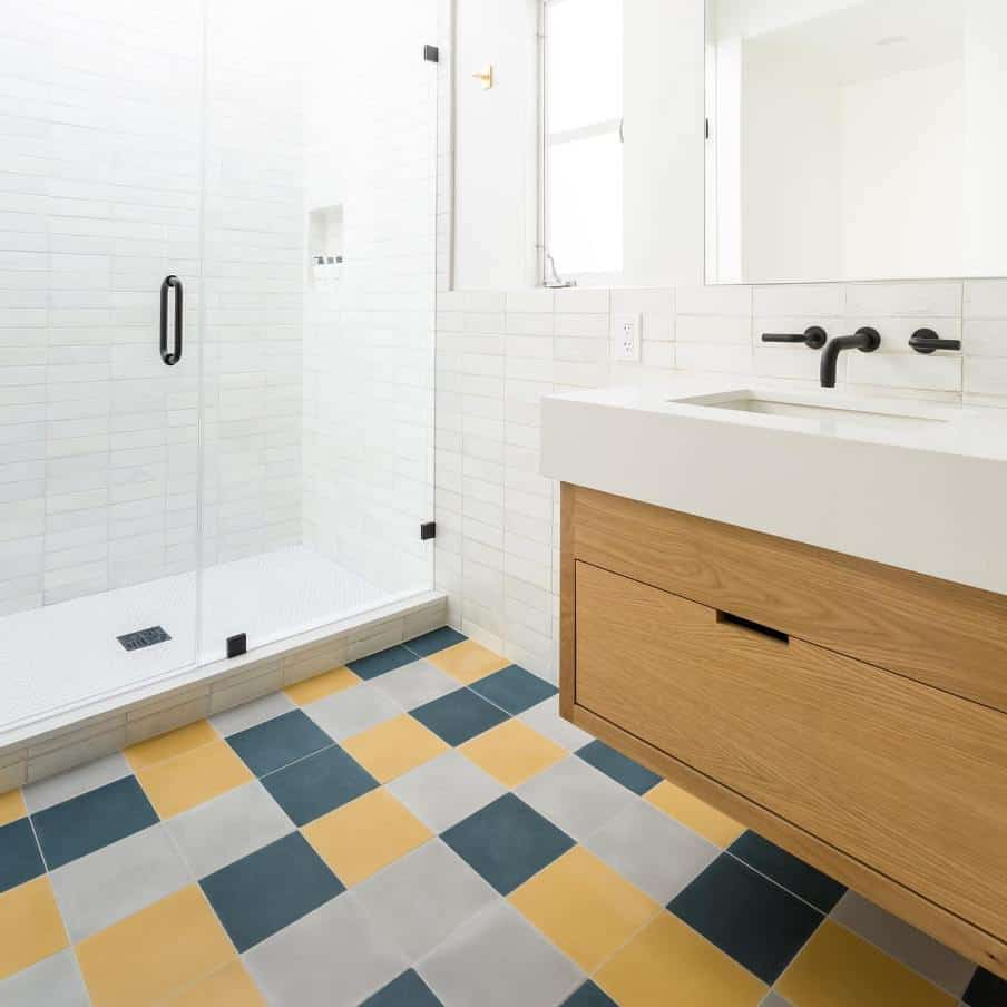 a white bathroom with oak sink furniture and multi colored floor tiles