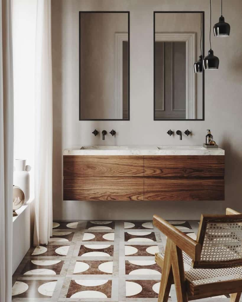 a bathroom setting showing a double sink unit in dark hardwood and gray walls with geometric pattern floor tiles