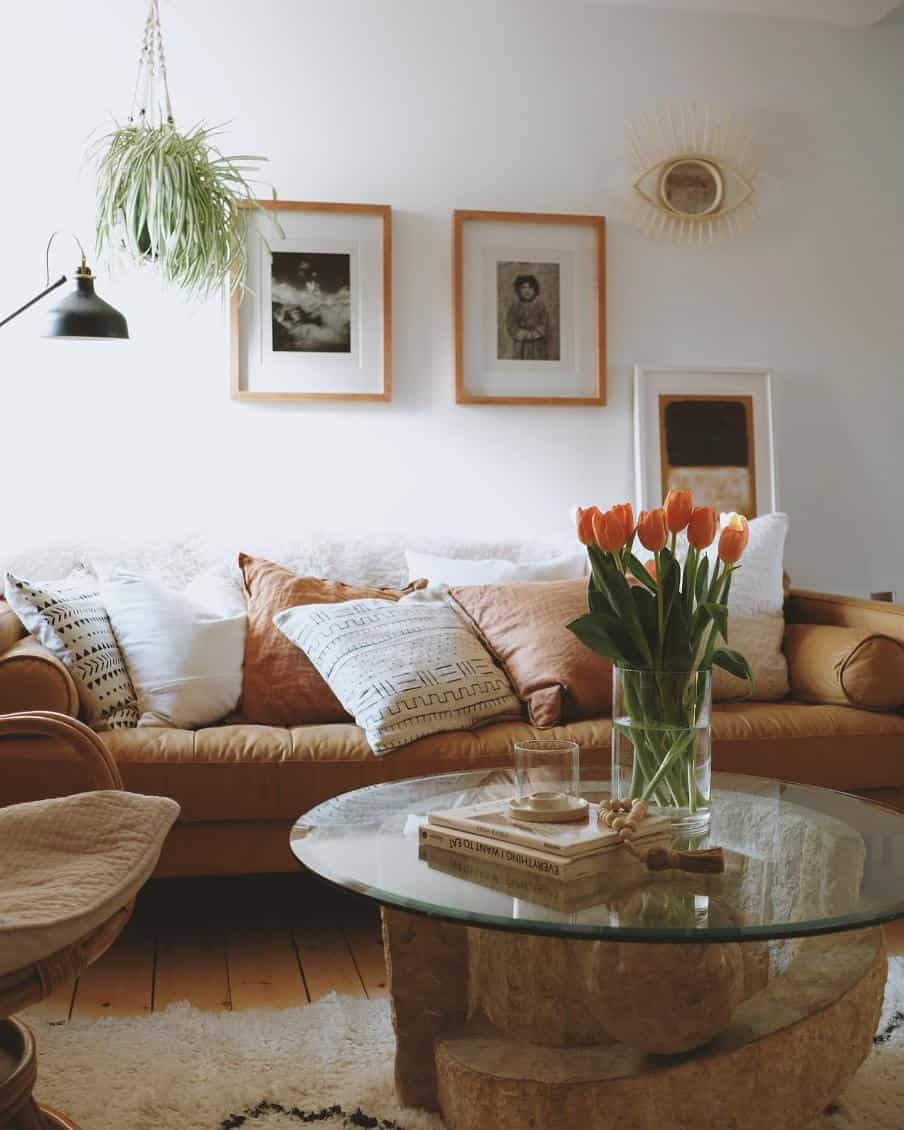 tan colored leather sofa with a circular glass topped coffee table in front