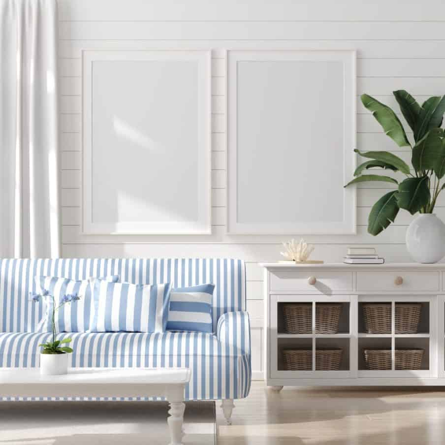 a white coastal inpired room with a blue striped sofa and cushions