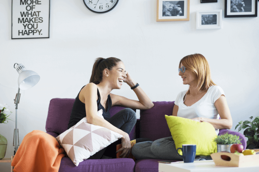 two women laughing on a blue sofa