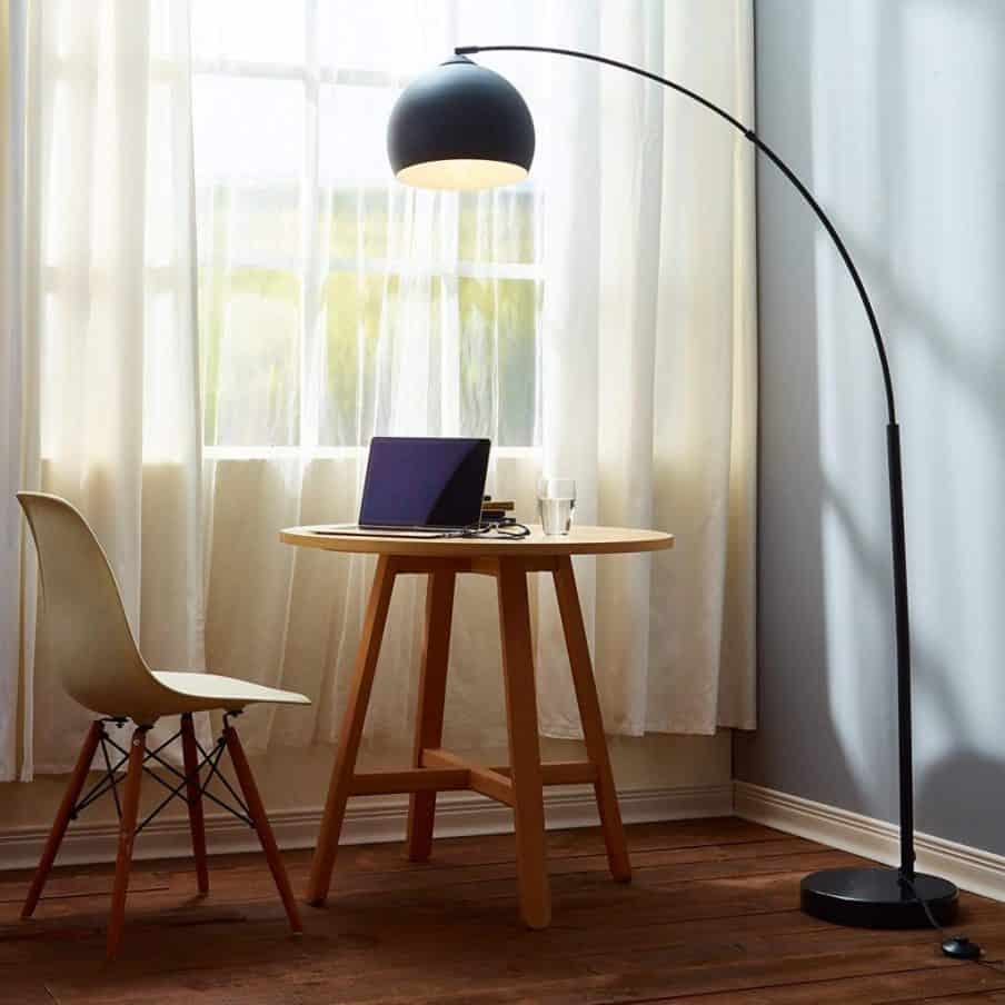 dark colored arch floor lamp over a small table and chair