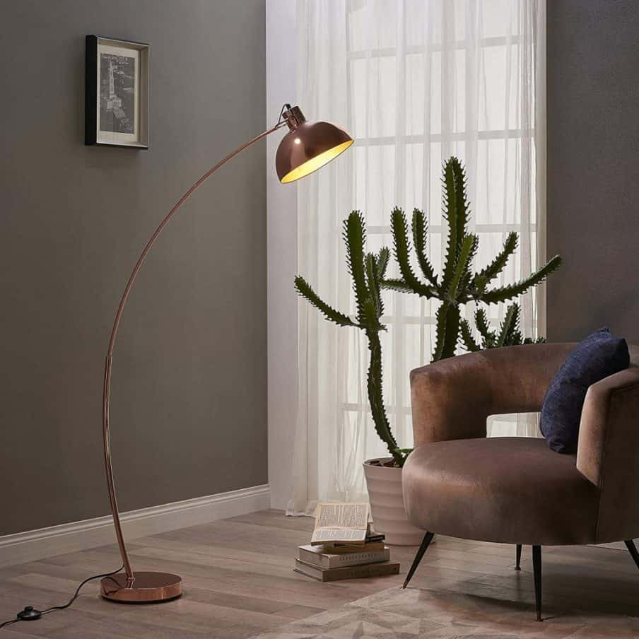 shorter arched floor lamp next to an armchair