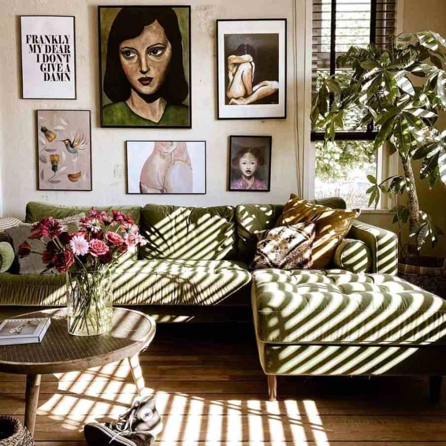 green velvet sofa with a wall of art behind