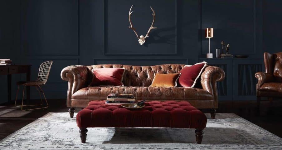 a large chesterfield sofa in a dark colored room