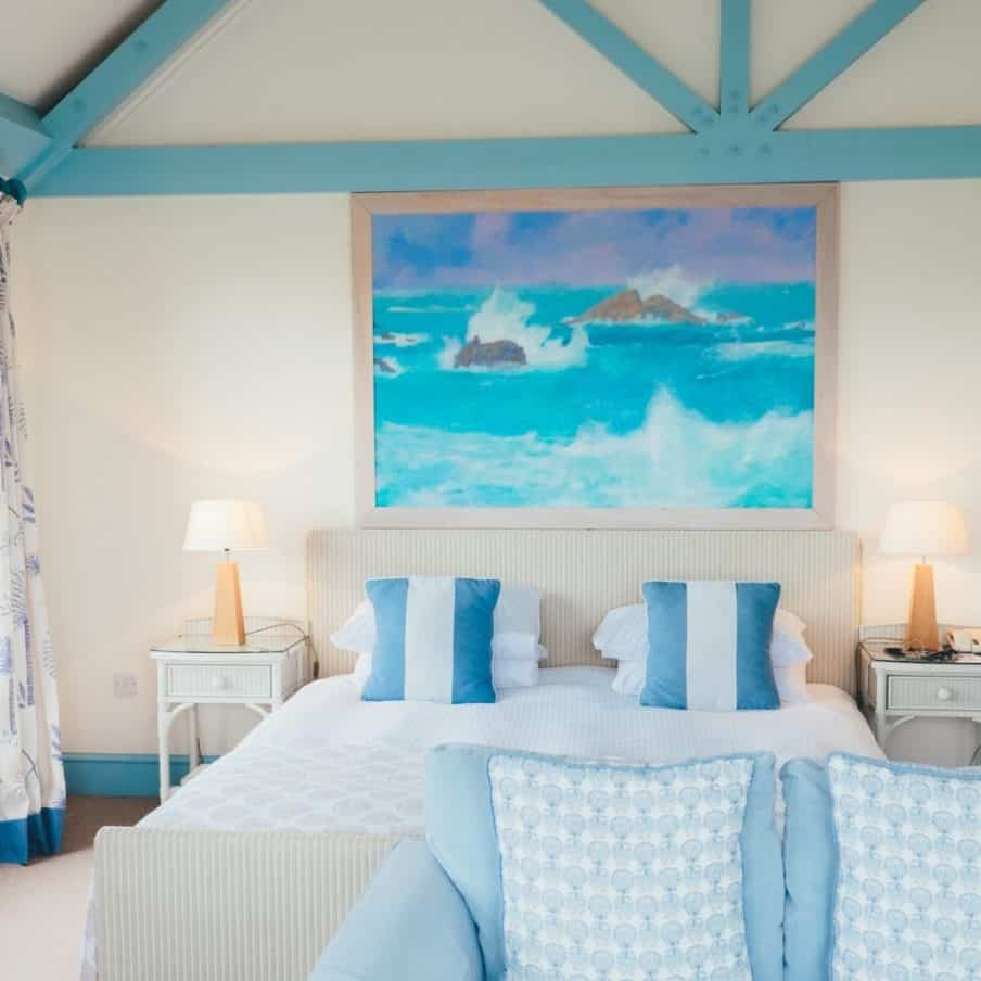 blue and white caostal themed bedoom with blue pictude above the bed