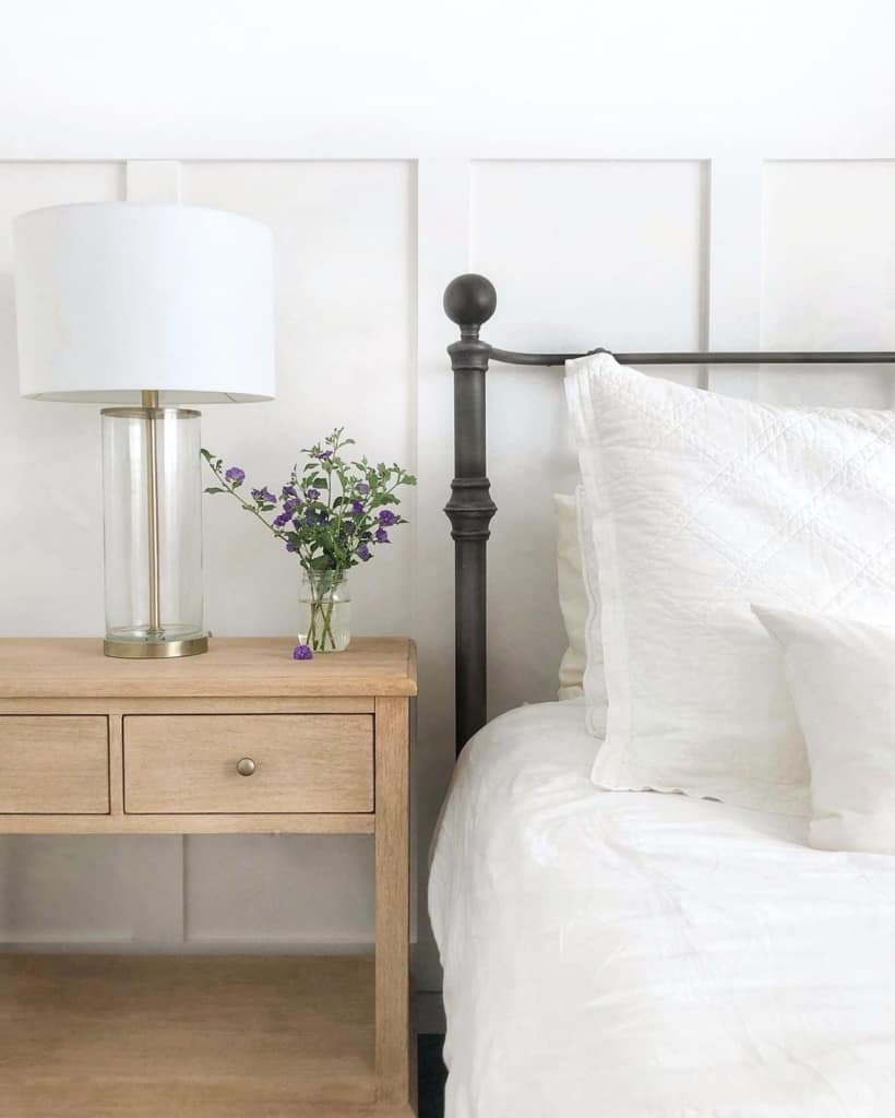 metal bedframe with white bedding and wooden nightstand