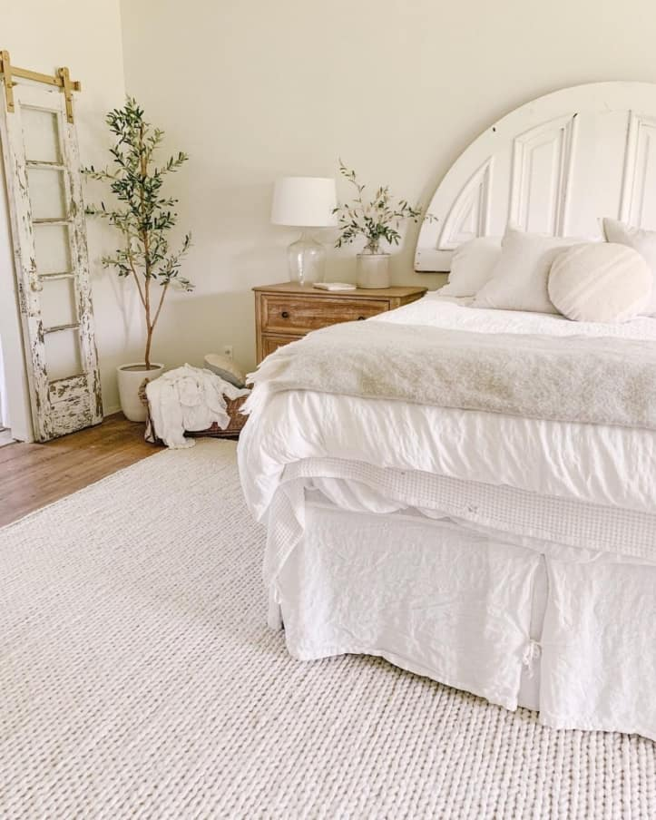 white bedroom with rug and plant