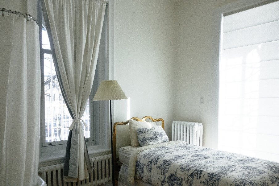single bed with colored cover in a white colored bedroom
