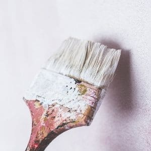 brush applying paint to a wall