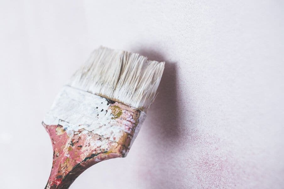paint brush loaded with paint against a painted wall