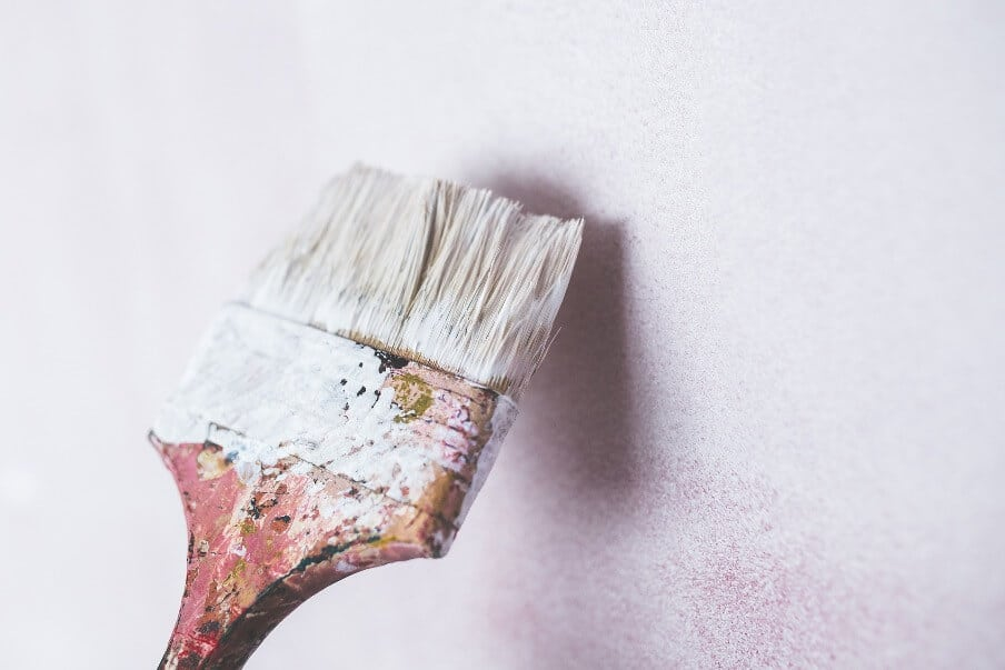 a paint brush against a painted wall