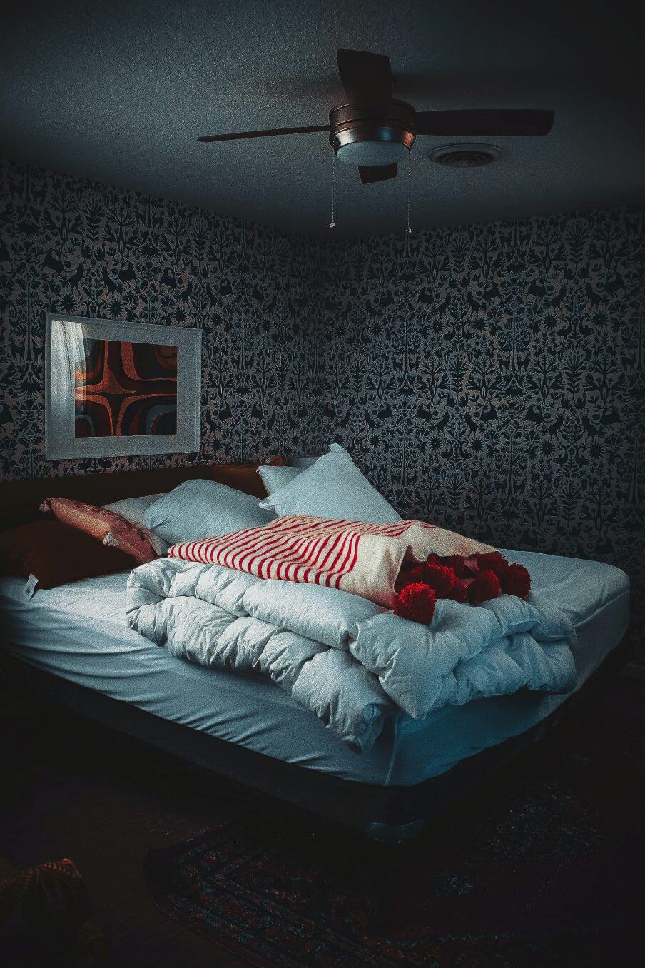 view of a dark bedroom with bed in the centre