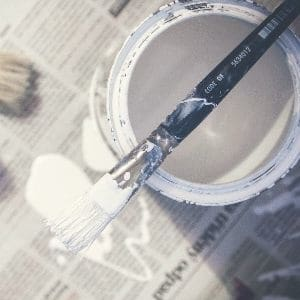 tin of whte paint and paint brush