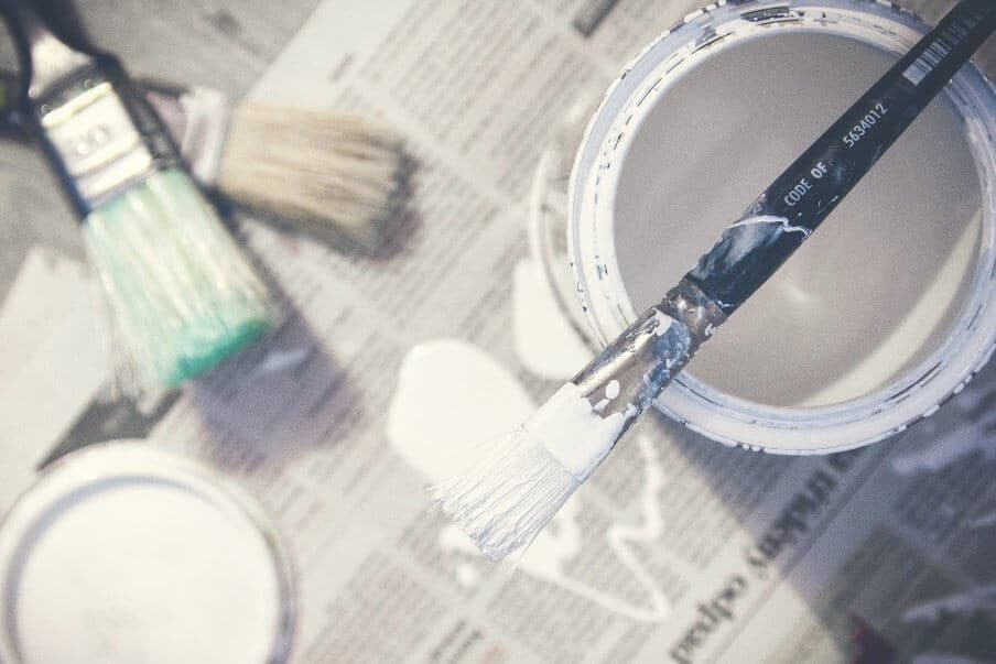 paint can and brushes with white paint