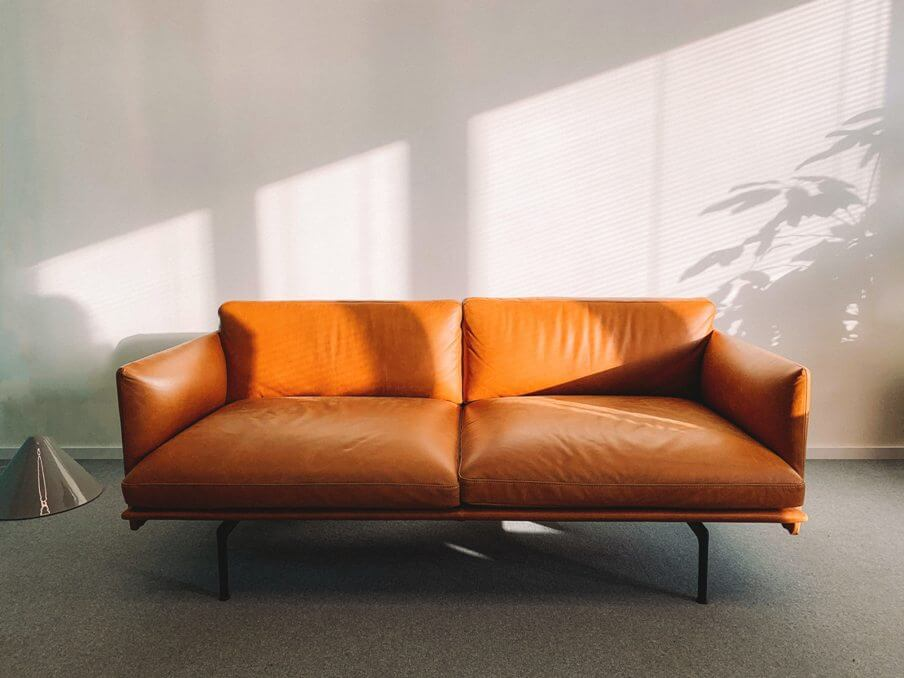 an orange leather sofa with sunlit wall behind