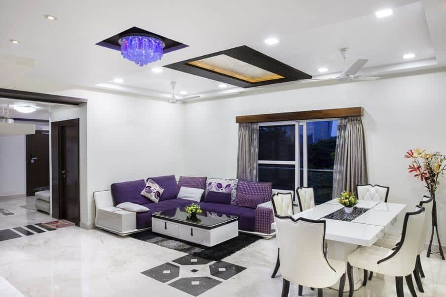 modern open plan living and dining area with marble floor and light colored furniture