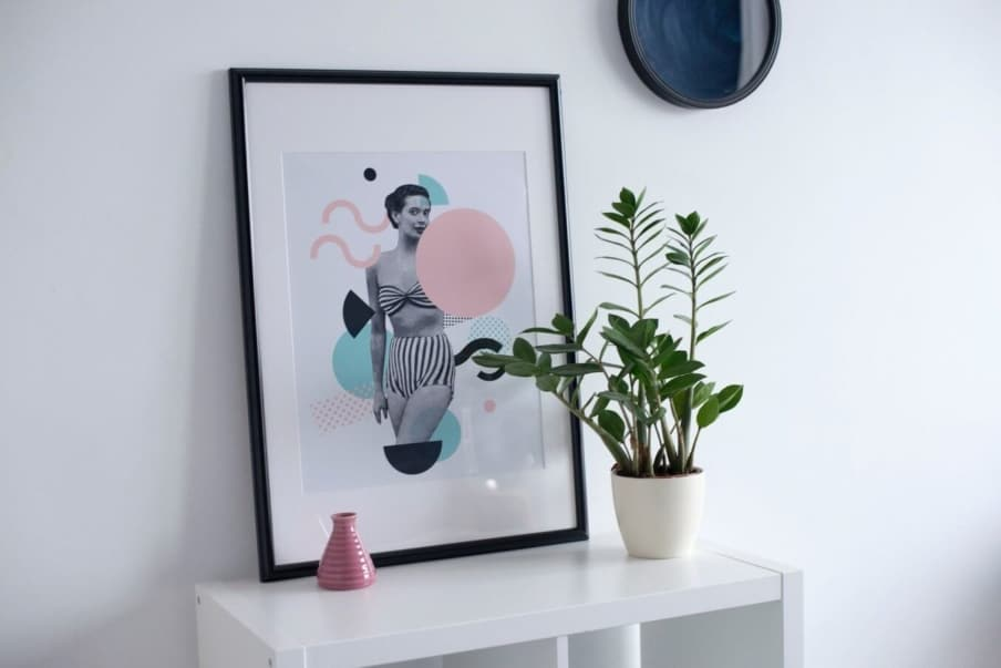 A colorful framed print sitting on a white unit and leaning against a white wall