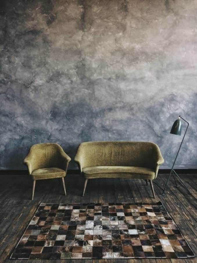 an armchair and a two seater sofa in green velvet set against a dark floor and wall