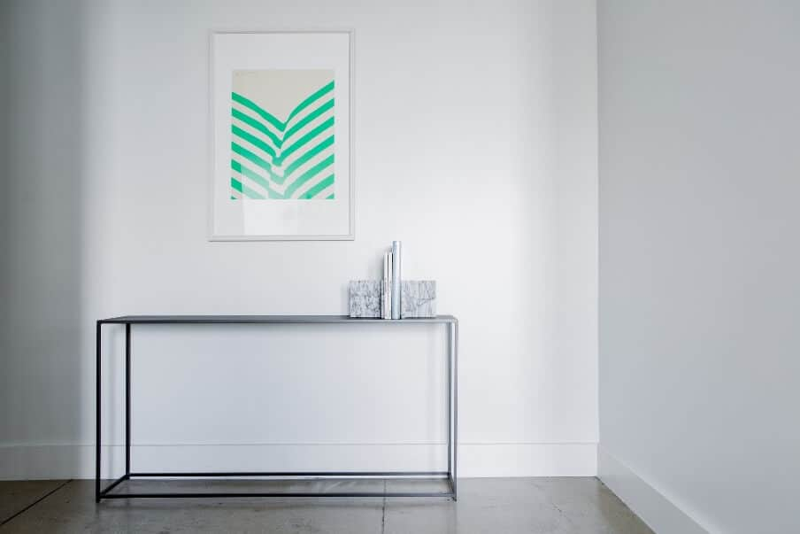 a frame table set against a white wall background
