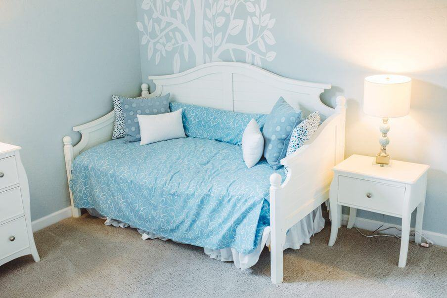 small daybed with blue cover in a bedroom setting with light blue walls